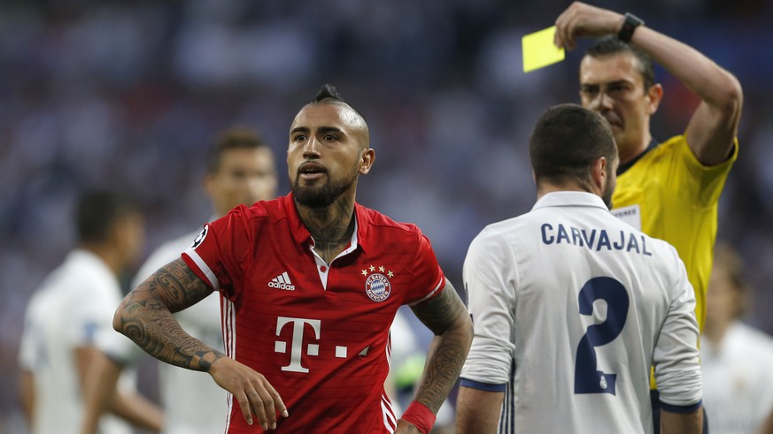 Referee Viktor Kassai of Hungary shows a yellow card to Bayern's Arturo Vidal, left, during the Champions League quarterfinal second leg soccer match between Real Madrid and Bayern Munich at Santiago Bernabeu stadium in Madrid, Spain, Tuesday April 18, 2017. (AP Photo/Francisco Seco)