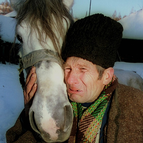 Nicolaie Maliar, 66, cries as he embraces his horse before selling it near Sigetul Marmatiei, in northern Romania, March 3, 2000.  Maliar, who owned the horse for eleven years, had to sell it for the equivalent of $550, because of financial problems. Maliar's pension is about $30 a month. (KEYSTONE/AP Photo/Vadim Ghirda)