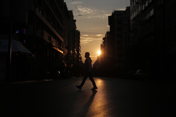 epa08822427 A pedestrian wearing a face mask is silhouetted against the setting sun as he crosses a street   during the second lockdown of the country, to stem the spread of the coronavirus pandemic, in central Athens, Greece, 15 November 2020. All outdoor gatherings were banned throughout Greece from Sunday 15 November at 06:00 until Wednesday 18 November at 21:00, at Greek police chiefs? order ahead of the Polytechnic uprising anniversary. The ban also foresees up to 5,000 fines for those that violate it either they are organizers or participants in any, over 4 people, gathering.  EPA/KOSTAS TSIRONIS