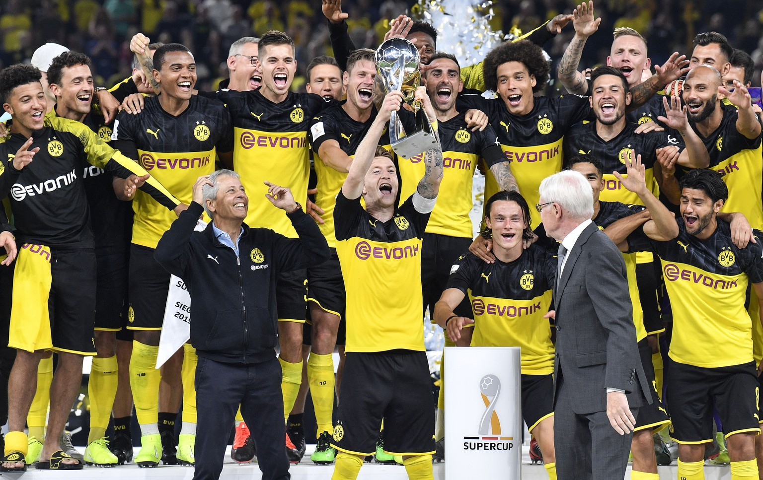 Dortmund's Marco Reus lifts up the trophy beside head coach Lucien Favre, left, and Dortmund's President Reinhard Rauball, right, as he celebrates with teammates after winning the German Super Cup final match between Borussia Dortmund and Bayern Munich in Dortmund, Germany, Saturday, Aug. 3, 2019. (AP Photo/Martin Meissner)
