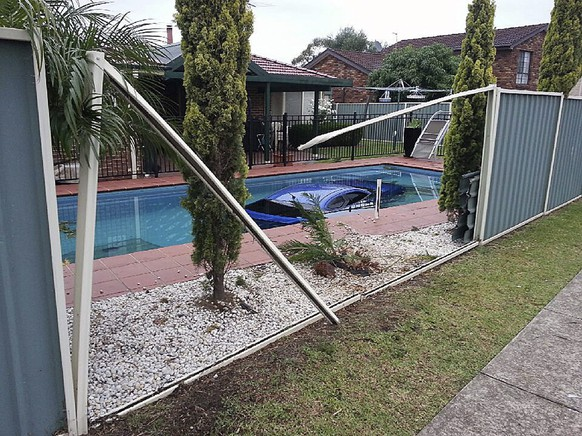 epa04690554 A handout image released by the New South Wales (NSW) police on 03 April 2015 shows a Mitsubishi Lancer that crashed through a fence and into a backyard pool in Hinchinbrook, southwest Sydney, Australia, 03 April  2015. The car mounted the kerb and drove into the pool after colliding with a taxi in Hinchinbrook in the early hours of 03 April. The 23-year-old driver and two passengers managed to get out of the car uninjured.  EPA/NSW POLICE AUSTRALIA AND NEW ZEALAND OUT -- Best available quality HANDOUT EDITORIAL USE ONLY