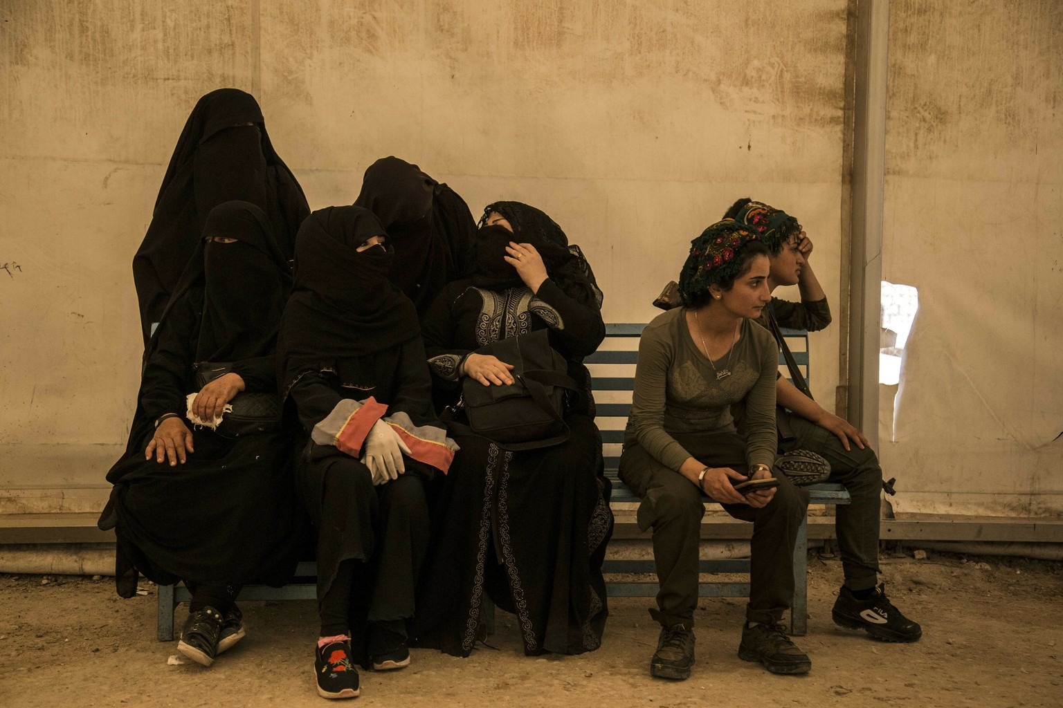 Women related to fighters of the Islamic State group sit next to Syrian Democratic Forces guards as they wait to board buses and trucks, leaving the overcrowded a an overcrowded al-Hol camp to return to their homes on Monday, June 3, 2019, in Hasakeh province, Syria. The departure is the largest since the IS group's territorial defeat in Syria in March, when the U.S.-backed SDF captured Baghouz, the last village controlled by the militants near the Iraqi border. (AP Photo/Baderkhan Ahmed)