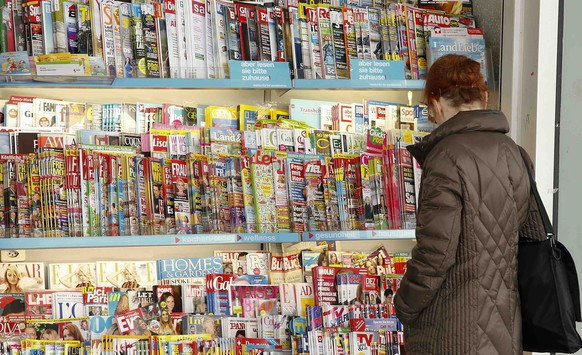 A woman looks at magazines displayed at a kiosk in Zurich March 16 , 2015. One of Switzerland's two big supermarkets, Coop, is to stop selling titles such as German magazine Der Spiegel, the German-language edition of Vogue and a Mickey Mouse comic because it says local distributors have not cut prices after a currency surge. The Swiss central bank's decision on Jan. 15 to end a cap on the value of the currency at 1.20 Swiss francs per euro sent the franc skyrocketing and led to fears for Switzerland's export-reliant economy. REUTERS/Arnd Wiegmann (SWITZERLAND - Tags: MEDIA BUSINESS)