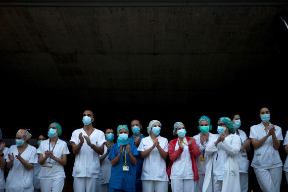 epa08358001 Members of the sanitary personnel clap during the daily gratitude applause for medical and health care personnel from a Saint Paul Hospital in Barcelona, Catalonia, Spain, 11 April 2020. Spain faces an atypical Holy Week, from 05 to 12 April, amid the coronavirus outbreak as churches are closed and religious processions were canceled. The country is on a 26th consecutive day of a mandatory home confinement in a bid to slow down the spread of the pandemic COVID-19 disease caused by the SARS-CoV-2.  EPA/ENRIC FONTCUBERTA