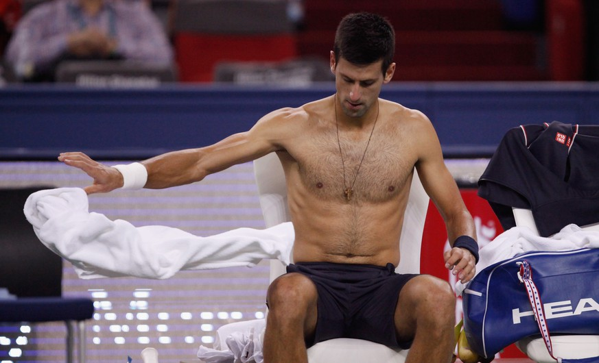 SHANGHAI, CHINA - OCTOBER 09: Novak Djokovic of Serbia changes his tee shirt after a game during his match against Mikhail Kukushkin of Kazakhstan during day 5 of the Shanghai Rolex Masters at Zi Zhong stadium on October 9, 2014 in Shanghai, China. (Photo by Kevin Lee/Getty Images)