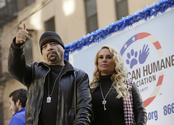 Rapper Ice-T gives a thumbs up with his wife Coco at his side as they ride aboard a float honoring retired military service animals during the 2014 annual Veterans Day parade in New York, Tuesday, Nov. 11, 2014. (AP Photo/Kathy Willens)