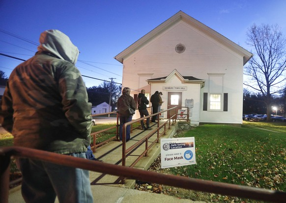 epa08795045 Voters wait in line before dawn and before the doors open at a polling location at the Edinburg Town Hall in Edinburg, Ohio, USA, 03 November 2020. Americans vote on Election Day to choose between re-electing Donald J. Trump or electing Joe Biden as the 46th President of the United States to serve from 2021 through 2024.  EPA/DAVID MAXWELL