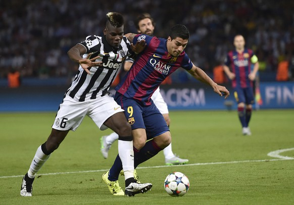 Juventus' Paul Pogba, left, and Barcelona's Luis Suarez challenge for the ball during the Champions League final soccer match between Juventus Turin and FC Barcelona at the Olympic stadium in Berlin Saturday, June 6, 2015. (AP Photo/Martin Meissner)