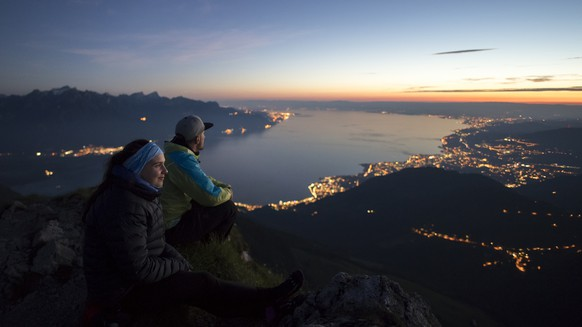Anais, left, and Anthony, right, watch the sunset from the Dent de Jaman mountain (1875m) above Montreux, Switzerland, with Lake Geneva in the background, on Sunday, June 11, 2017. (KEYSTONE/Anthony Anex)