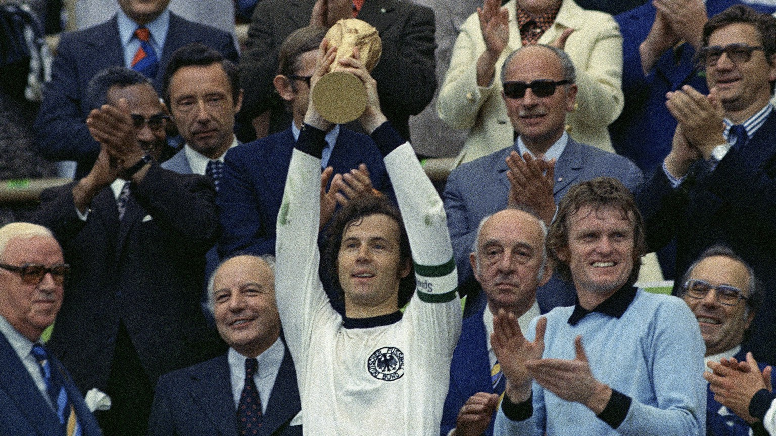 FILE - In this July 7, 1974 file photo, West Germany captain, Franz Beckenbauer, holds up the World Cup trophy after his team defeated the Netherlands by 2-1, in the World Cup soccer final at Munich's Olympic stadium, in West Germany. Applauding at right, German goalkeeper Josef