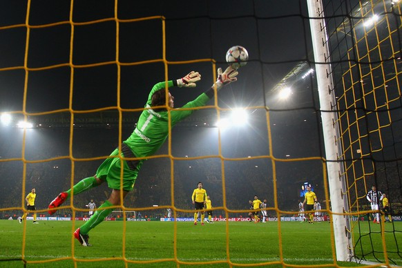 DORTMUND, GERMANY - MARCH 18:  Roman Weidenfeller of Borussia Dortmund dives in vain as Carlos Tevez of Juventus scores the opening goal during the UEFA Champions League Round of 16 between Borussia Dortmund and Juventus at Signal Iduna Park on March 18, 2015 in Dortmund, Germany.  (Photo by Alex Grimm/Bongarts/Getty Images)