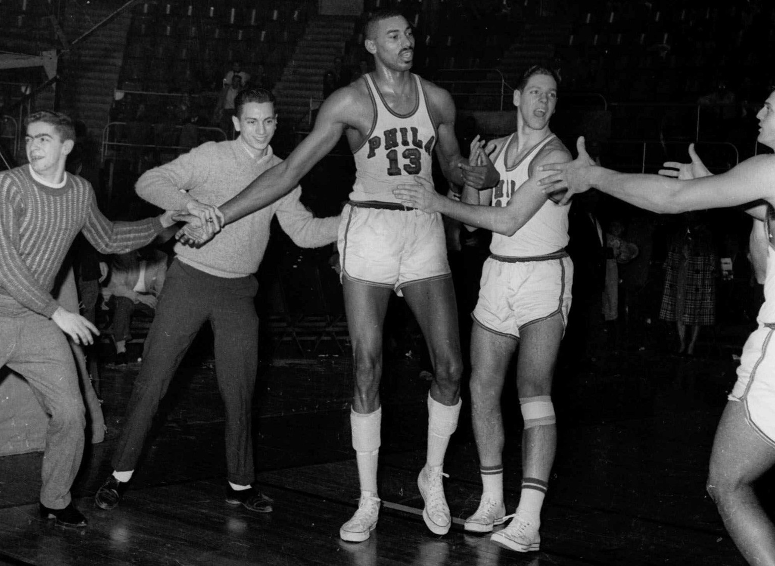 FILE -- Wilt Chamberlain (13) of the Philadelphia Warriors, is congratulated by unidentified teammates and fans who rushed onto the floor in Hershey, Pa., after Chamberlain scored his 100th points for an NBA record, in this March 2, 1962 photo. Chamberlain, one of the most dominant players in the history of basketball died Tuesday Oct. 12, 1999 at age 63, a Los Angeles Lakers spokesman said. (AP Photo/File)