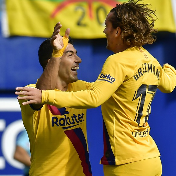Barcelona's Antoine Griezmann, right, celebrates with Luis Suarez after scoring the opening goal during a Spanish La Liga soccer match between Eibar and FC Barcelona at the Ipurua stadium in Eibar, Spain, Saturday Oct. 19, 2019. (AP Photo/Alvaro Barrientos)