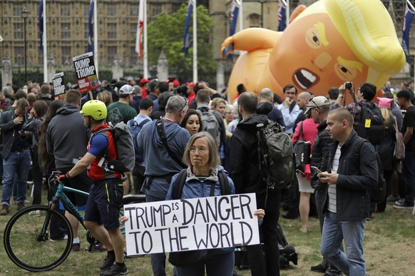 A woman holds a placard as the 'Trump Baby' blimp is inflated in Parliament Square in central London as people start to gather to demonstrate against the state visit of President Donald Trump, Tuesday, June 4, 2019. Trump will turn from pageantry to policy Tuesday as he joins British Prime Minister Theresa May for a day of talks likely to highlight fresh uncertainty in the allies' storied relationship. (AP Photo/Matt Dunham)