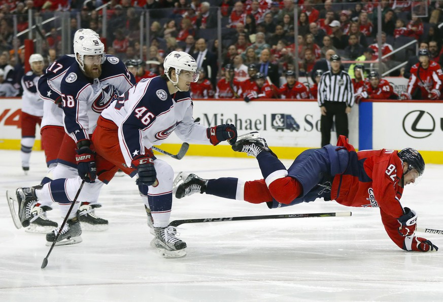 Washington Capitals center Evgeny Kuznetsov (92) is tripped by Columbus Blue Jackets defenseman Dean Kukan (46) during the second period of an NHL hockey game Friday, Feb. 9, 2018, in Washington. Blue Jackets center Brandon Dubinsky (17) and defenseman David Savard (58) look on. (AP Photo/Pablo Martinez Monsivais)