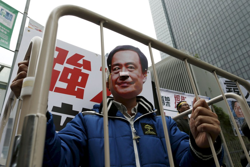 A demonstrator wears a mask depicting Causeway Bay Books shareholder Lee Bo during a protest over the disappearance of booksellers, in Hong Kong, China in this January 10, 2016 file photo. Britain said on February 12, 2016 that a missing Hong Kong seller of gossipy books on China's leaders had likely been