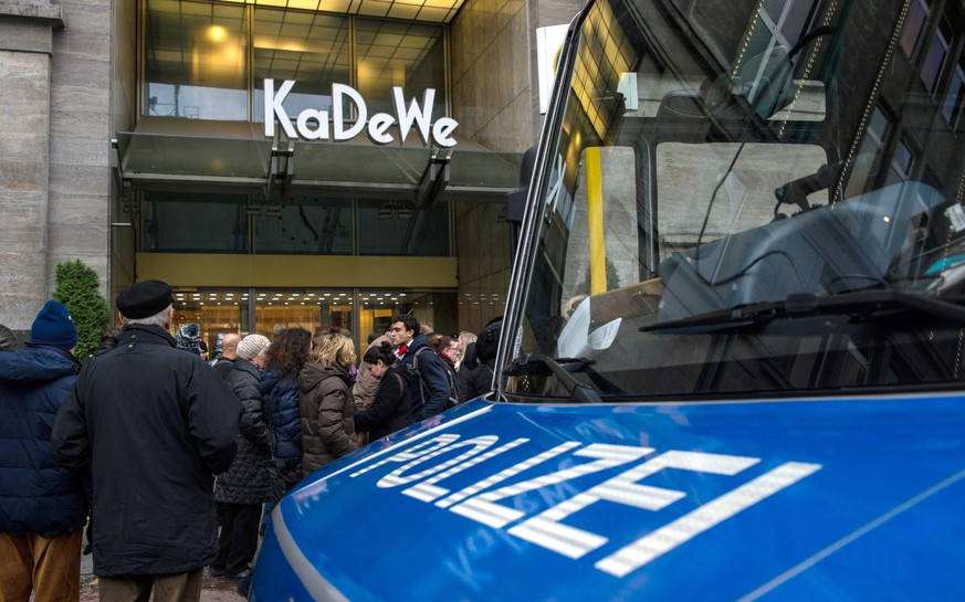 epa04535689 Policemen stand in front of the department store KaDeWe (Kaufhaus des Westens, Department Store of the West) behind a barrier in Berlin, Germany, 20 December 2014. Four robbers entered the luxury department store in the German capital and fired tear gas at staff and Christmas shoppers in the jewellery section before fleeing in a car. The store, which is a major tourist attraction, was shut down for about two hours after the incident. Police are trying to locate the robbers, whom one witness saw speeding away in a black car, a newspaper said.  EPA/PAUL ZINKEN