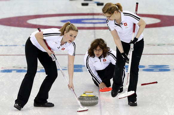 Switzerland's skip Mirjam Ott, center, watches as Janine Greiner, right, and Alina Paetz, right, sweep the ice during the women's curling competition against Britain at the 2014 Winter Olympics, Saturday, Feb. 15, 2014, in Sochi, Russia. (AP Photo/Wong Maye-E)