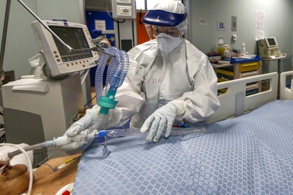 A medical staffer tends to a patient in the ICU unit of the Covid 3 hospital in Casalpalocco, near Rome, Saturday, April 11, 2020. Italy has topped 19,000 deaths and 150,000 cases of coronavirus. The milestones were hit Saturday, even as the country continued to see a slight decrease in numbers of people hospitalize and in intensive care. The new coronavirus causes mild or moderate symptoms for most people, but for some, especially older adults and people with existing health problems, it can cause more severe illness or death. (Cecilia Fabiano/LaPresse via AP)