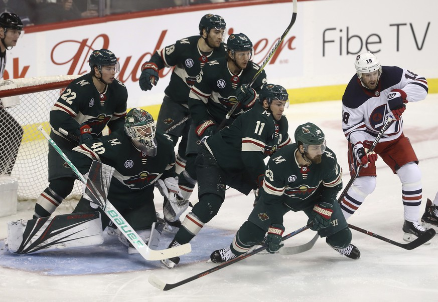 Minnesota Wild's Kevin Fiala (22), goaltender Devan Dubnyk (40), Luke Kunin (19), Jonas Brodin (25), Zach Parise (11) and Greg Pateryn (29) gather in front of the net as Winnipeg Jets' Bryan Little (18) looks for the puck during the first period of an NHL hockey game Tuesday, Feb. 26, 2019, in Winnipeg, Manitoba. (Trevor Hagan/The Canadian Press via AP)