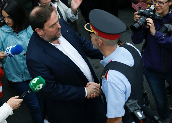 epa06237401 Catalan Deputy Premier, Oriol Junqueras (L), greets a Catalan policeman or Mosso d'Esquadra as he arrives to the Sant Jordi School to vote in the '1-O Referendum' in Sant Vicent dels Horts, Catalonia, northeastern Spain, on 01 October 2017. Meanwhile, National Police officers and Civil guards have been deployed to prevent the people from entering to the polling centers and vote in the Catalan independence referendum, that has been banned by the Spanish Constitutional Court, what has provocked clashes between pro-independence people and the police forces in some polling centers. EFE/Alejandro Garcia  EPA/ALEJANDRO GARCIA