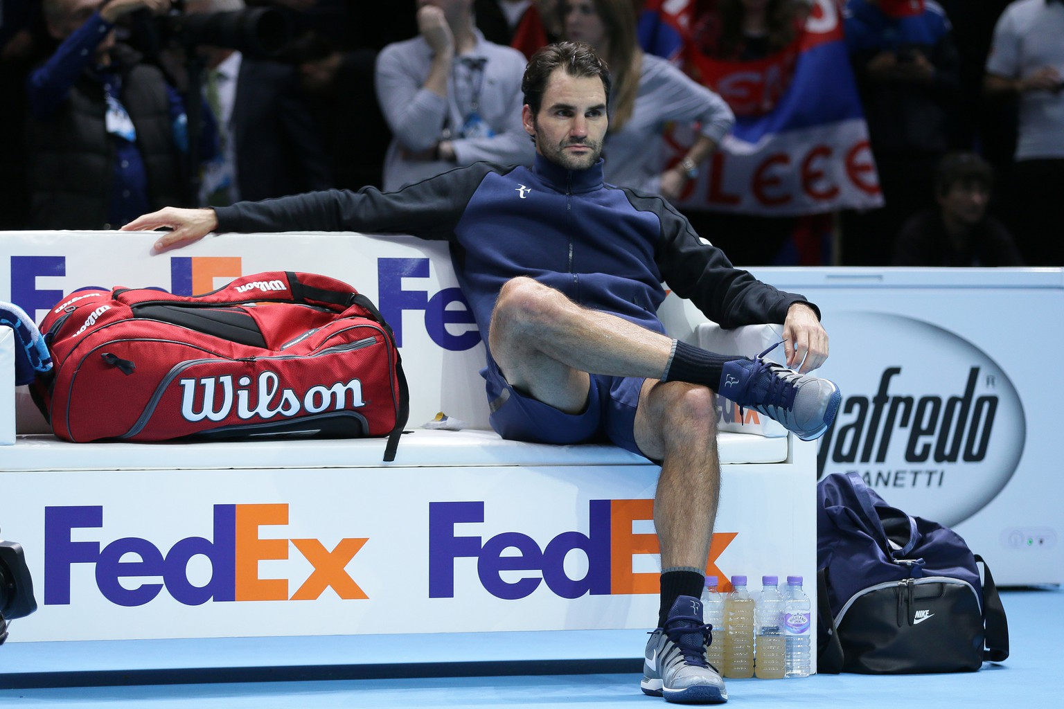 Roger Federer of Switzerland waits for the trophy ceremony after losing to Novak Djokovic of Serbia in their ATP World Tour Finals final tennis match at the O2 Arena in London, Sunday Nov. 22, 2015. (AP Photo/Tim Ireland)