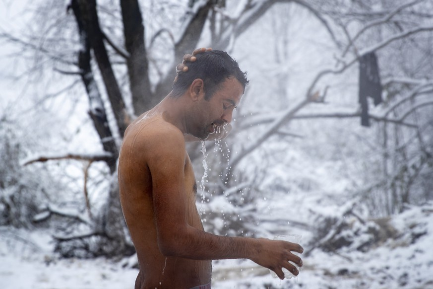 Aftab Tariq, 27, from Pakistan, takes a shower at the Vucjak refugee camp outside Bihac, northwestern Bosnia, Tuesday, Dec. 3, 2019. A top European human rights official has demanded immediate closure of a migrant camp in Bosnia where hundreds of people have refused food and water to protest lack of protection in snowy and cold weather. (AP Photo/Darko Bandic)
