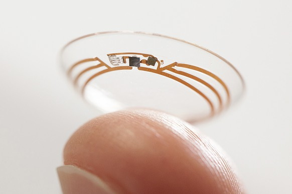 This undated photo released by Google shows a contact lens Google is testing to explore tear glucose. After years of scalding soldering hair-thin wires to miniaturize electronics, Brian Otis, Google X project lead, has burned his fingertips so often that he can no longer feel the tiny chips he made from scratch in Google's Silicon Valley headquarters, a small price to pay for what he says is the smallest wireless glucose sensor that has ever been made. (AP Photo/Google)