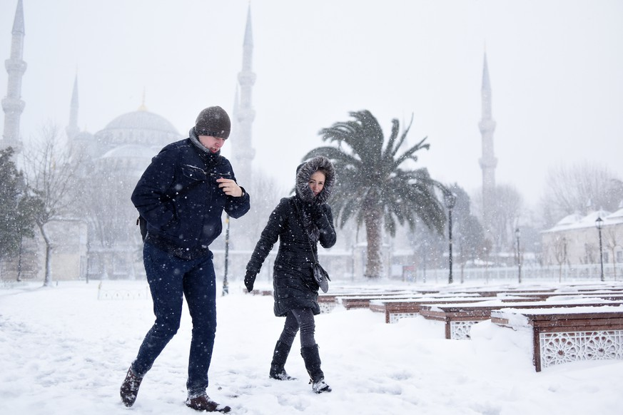People walk in the snow, in the historic Sultanahmet district in Istanbul, Saturday, Jan. 7, 2017. Heavy snow clogged roads, shipping traffic in Bosphorus and forced hundreds of flight cancellations in the Turkish metropolis. (Mert Akyol/Depo Photos via AP)