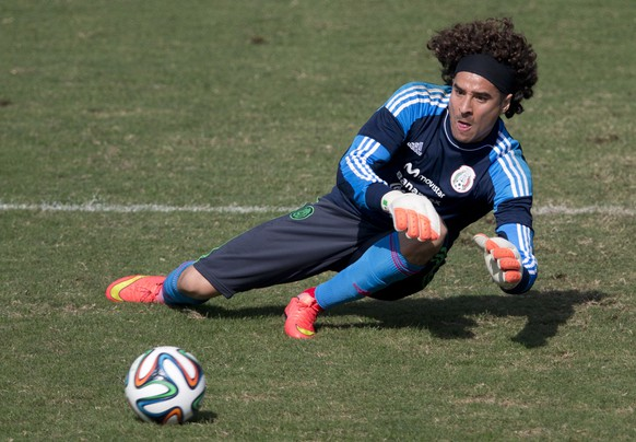 Mexico goalkeeper Guillermo Ochoa leaps to trap a ball during a training session in Santos, Brazil, Thursday, June 26, 2014. Mexico will face the Netherlands in their next World Cup match in Fortaleza, Sunday.