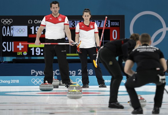 Switzerland Martin Rios, left, and Jenny Perret, second from left, watch Russian athletes during their mixed doubles curling semi-final match at the 2018 Winter Olympics in Gangneung, South Korea, Monday, Feb. 12, 2018. (AP Photo/Aaron Favila)