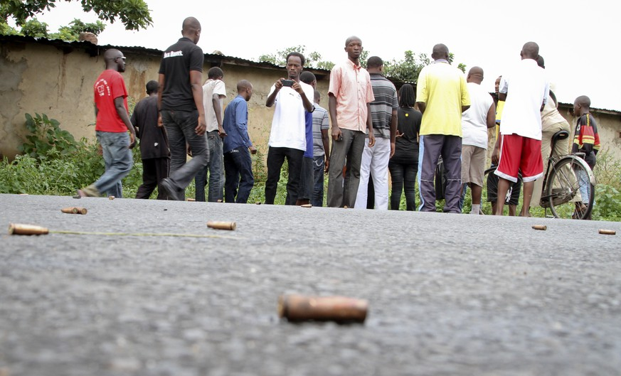 A man looks across at spent bullet casings lying on a street in the Nyakabiga neighborhood of Bujumbura, Burundi, Saturday, Dec. 12, 2015. Burundi's political violence continued Saturday as a number of people were found shot dead in the Nyakabiga neighborhood of the capital, a day after the government said an unidentified group carried out coordinated attacks on three military installations. (AP Photo)