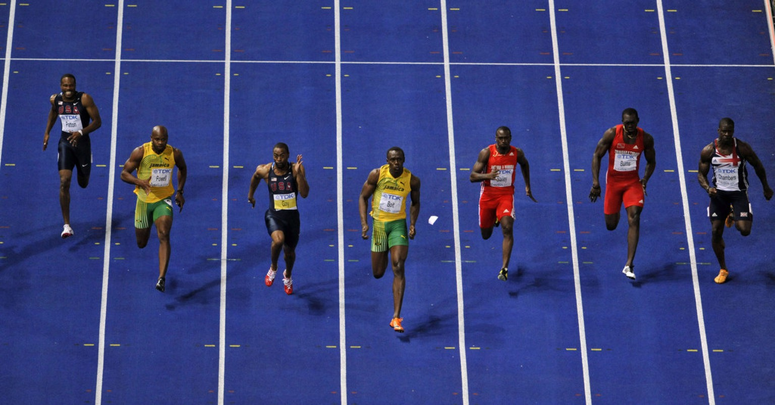 Jamaica's Usain Bolt, center, runs to setting a new Men's 100m World Record during the World Athletics Championships in Berlin on Sunday, Aug. 16, 2009.  (AP Photo/Gero Breloer)