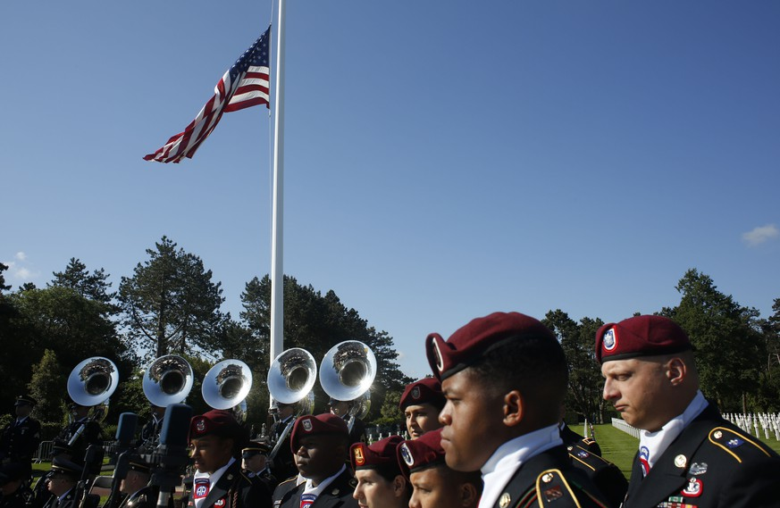 US Army soldiers, based in Germany, stand near the American flag prior to a ceremony to mark the 75th anniversary of D-Day at the Normandy American Cemetery in Colleville-sur-Mer, Normandy, France, Thursday, June 6, 2019. World leaders are gathered Thursday in France to mark the 75th anniversary of the D-Day landings. (AP Photo/Thibault Camus)