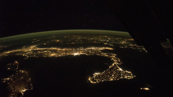 The easily recognized boot of Italy, with Sicily at its toe, is spread across this panorama taken by astronauts aboard the International Space Station. On a clear night looking east, the pattern of night lights shows populations concentrated mainly along the coastlines, but also in the Po River Valley of northern Italy.Some of the brightest clusters of lights are Rome and nearby Naples, with island cities of Cagliari on Sardinia and Catania on Sicily—now well-known as the hometown of European Space Agency astronaut Luca Parmitano.The small, dark, circular patch dangerously close to Catania marks the unpopulated slopes of the active volcano Etna. Hazy lights, as over the Po valley and Rome, probably indicate thin clouds above. The island of Malta appears at the lower right.The airglow line is vivid in this night shot.A more detailed image of the toe and heel of Italy at night can be viewed here.A daytime image of Etna erupting ash and steam can be viewed here.Astronaut photograph ISS041-E-90188 was acquired on October 21, 2014, with a Nikon D4 digital camera using a 24 millimeter lens, and is provided by the ISS Crew Earth Observations Facility and the Earth Science and Remote Sensing Unit, Johnson Space Center. The image was taken by the Expedition 42 crew. It has been cropped and enhanced to improve contrast, and lens artifacts have been removed. The International Space Station Program supports the laboratory as part of the ISS National Lab to help astronauts take pictures of Earth that will be of the greatest value to scientists and the public, and to make those images freely available on the Internet. Caption by M. Justin Wilkinson, Jacobs at NASA-JSC. *** Please Use Credit from Credit Field ***
