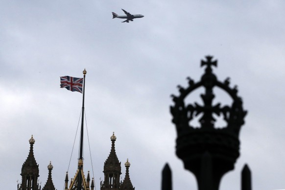 FILE - In this file photo dated Saturday, Dec. 14, 2019, a British flag waves atop of Houses of Parliament as an aircraft approaches the airport in London.  After nearly five decades of economic and social integration, from the start of 2021 Britain will embark on a more-distant relationship with the European Union, and freedom of movement seems set to dramatically change for people wanting to cross the English Channel. (AP Photo/Thanassis Stavrakis, FILE)