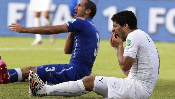 epa04353260 (FILE) A file picture dated 24 June 2014 of Italy's Giorgio Chiellini (L) claiming he was bitten by Uruguay's Luis Suarez (R) during the FIFA World Cup 2014 group D preliminary round match between Italy and Uruguay at the Estadio Arena das Dunas in Natal, Brazil. The International Court of Arbitration for Sport (CAS) on 14 August 2014 announced that Luis Suarez' four-month ban for biting Italy's Giorgio Chiellini at the Brazil FIFA World Cup 2014 is upheld, but the Uruguayan striker is allowed to train at his new club FC Barcelona.    (RESTRICTIONS APPLY: Editorial Use Only, not used in association with any commercial entity - Images must not be used in any form of alert service or push service of any kind including via mobile alert services, downloads to mobile devices or MMS messaging - Images must appear as still images and must not emulate match action video footage - No alteration is made to, and no text or image is superimposed over, any published image which: (a) intentionally obscures or removes a sponsor identification image; or (b) adds or overlays the commercial identification of any third party which is not officially associated with the FIFA World Cup)  EPA/EMILIO LAVANDEIRA JR   EDITORIAL USE ONLY *** Local Caption *** 51441129