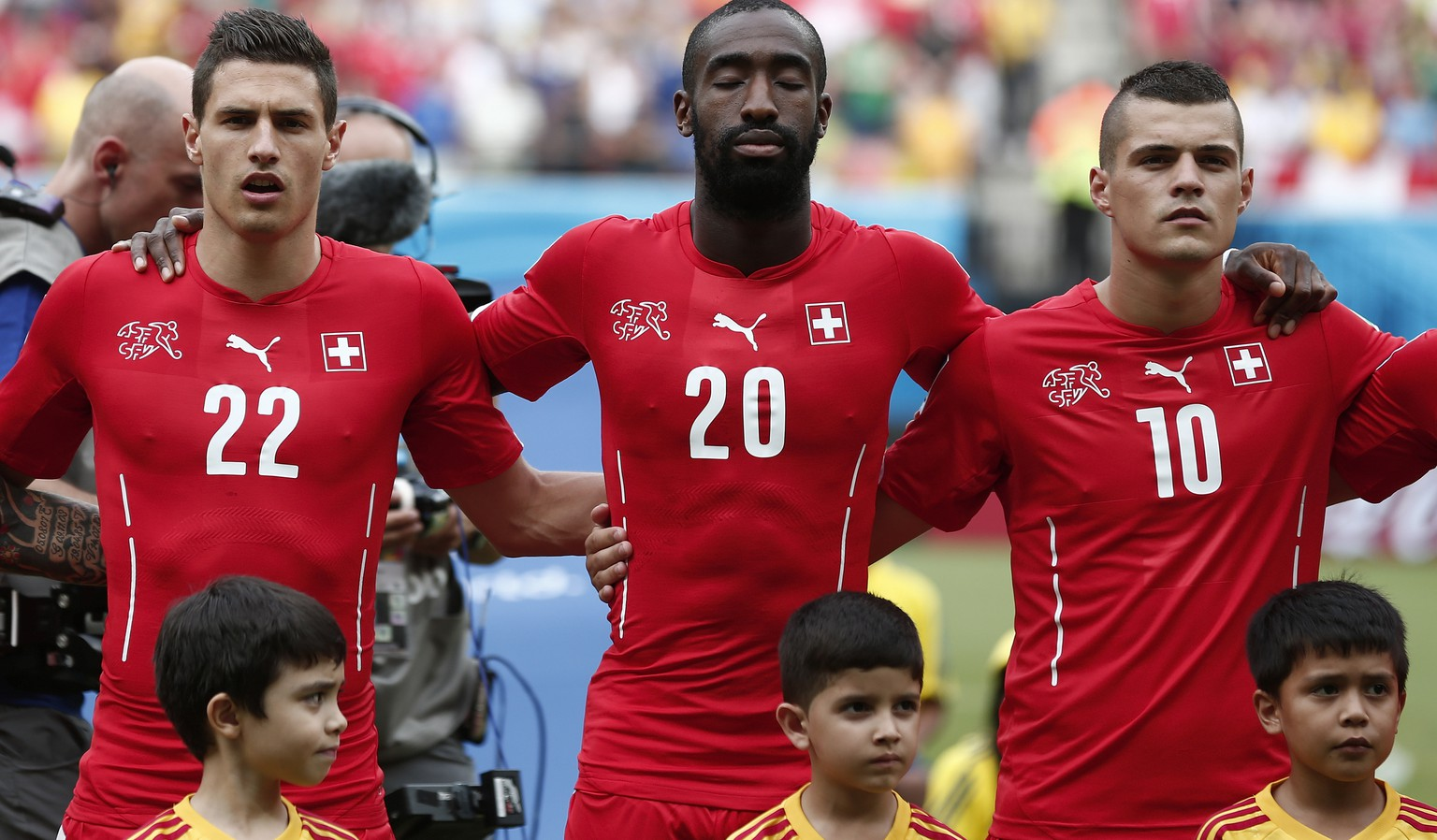 From left: Switzerland's Fabian Schaer, Johan Djourou and Granit Xhaka listen to the national anthem prior to the group E preliminary round match between Switzerland and Honduras in the Arena da Amazonia in Manaus, Brazil, Wednesday, June 25, 2014. (KEYSTONE/Peter Klaunzer)