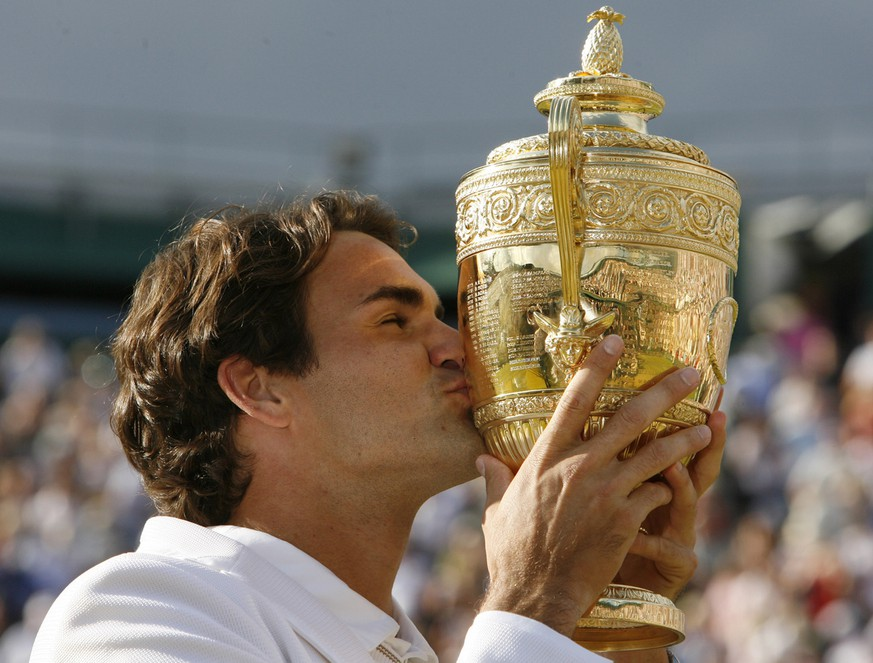 Switzerland's Roger Federer kisses the trophy after defeating Rafael Nadal to win his fifth consecutive Men's Singles Championship on the Centre Court at Wimbledon, Sunday July 8, 2007.(AP Photo/Anja Niedringhaus) ** EDITORIAL USE ONLY **