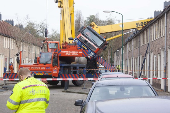 A picture taken on December 13, 2014 in IJsselstein shows a crane which fell down on to the roof of a house. The incident occurred when a man tried to surprise his girlfriend by proposing from the top of the crane, which then toppled on to the house, though no injuries were reported.    AFP PHOTO / ANP / GINOPRESS netherlands out