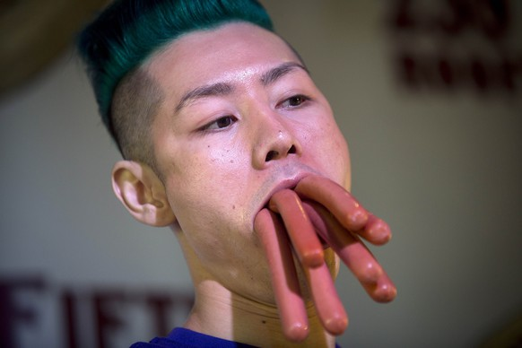 Takeru Kobayashi poses for a photo following his victory in a bunless hot dog eating competition in the Manhattan borough of New York July 4, 2014. Kobayashi ate 113 hotdogs in what organizers claim is the world's first official bunless hotdog eating competition. The competition was a counter event to Nathan's Famous Fourth of July International Hot Dog-Eating Contest at Coney Island. Hotdog eating champs, backyard picnickers and small-town parade lovers pressed on with July Fourth celebrations, some with less sizzle after wet weather on the U.S. East Coast postponed fireworks shows.    REUTERS/Carlo Allegri (UNITED STATES - Tags: SOCIETY ENVIRONMENT FOOD TPX IMAGES OF THE DAY)