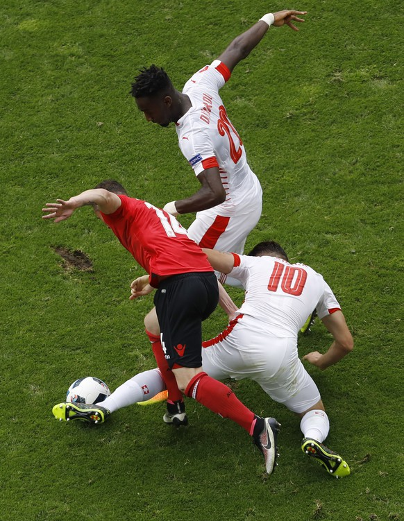 Switzerland's Granit Xhaka, right and his brother playing for AlbaniaTaulant Xhaka fight for the ball during the Euro 2016 Group A soccer match between Albania and Switzerland, at the Bollaert stadium in Lens, France, Saturday, June 11, 2016. On top is Switzerland's Johan Djourou. (AP Photo/Darko Vojinovic)