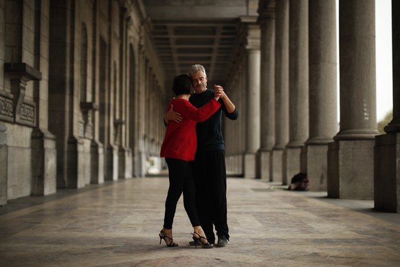 A couple dances the tango on the arcade of the Royal Military museum at Cinquantenaire park in Brussels, Wednesday, Nov. 11, 2020. This autumn, Belgium was the European country with the highest number of coronavirus cases per 100,000 cases at some point but the situation has been gradually improving over the past seven days. (AP Photo/Francisco Seco)