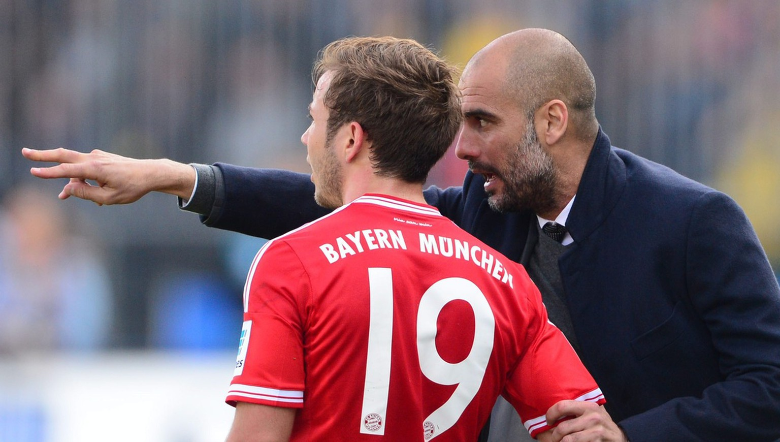 epa04172706 Munich's head coach Pep Guardiola (R) talks to his player Mario Goetze during the German Bundesliga soccer match between Eintracht Braunschweig and FC Bayern Munich at Eintracht Stadium in Braunschweig, Germany, 19 April 2014. ..(ATTENTION: Due to the accreditation guidelines, the DFL only permits the publication and utilisation of up to 15 pictures per match on the internet and in online media during the match.)  EPA/PETER STEFFEN