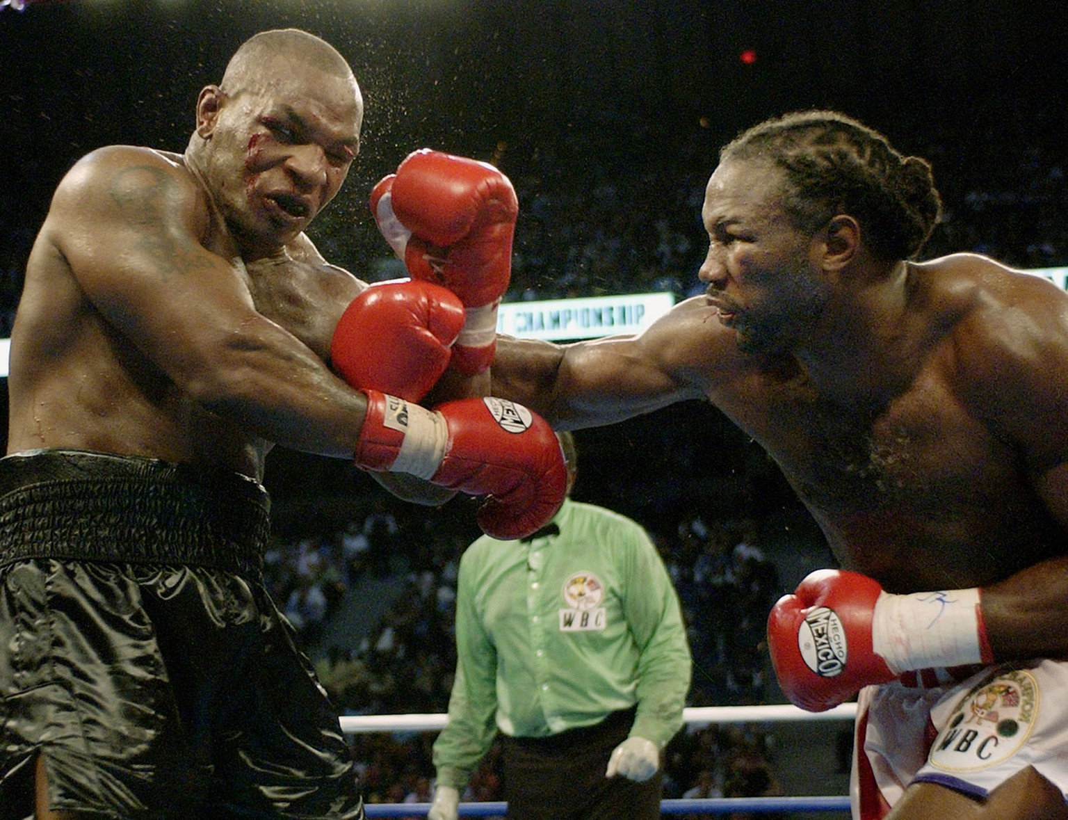 Mike Tyson, left, reels back after a right from Lennox Lewis during the seventh round of their WBC/IBF heavyweight championship bout at The Pyramid in Memphis, Tenn., Saturday, June 8, 2002. Lewis knocked down Tyson in the eighth round. (AP Photo/Laura Rauch)