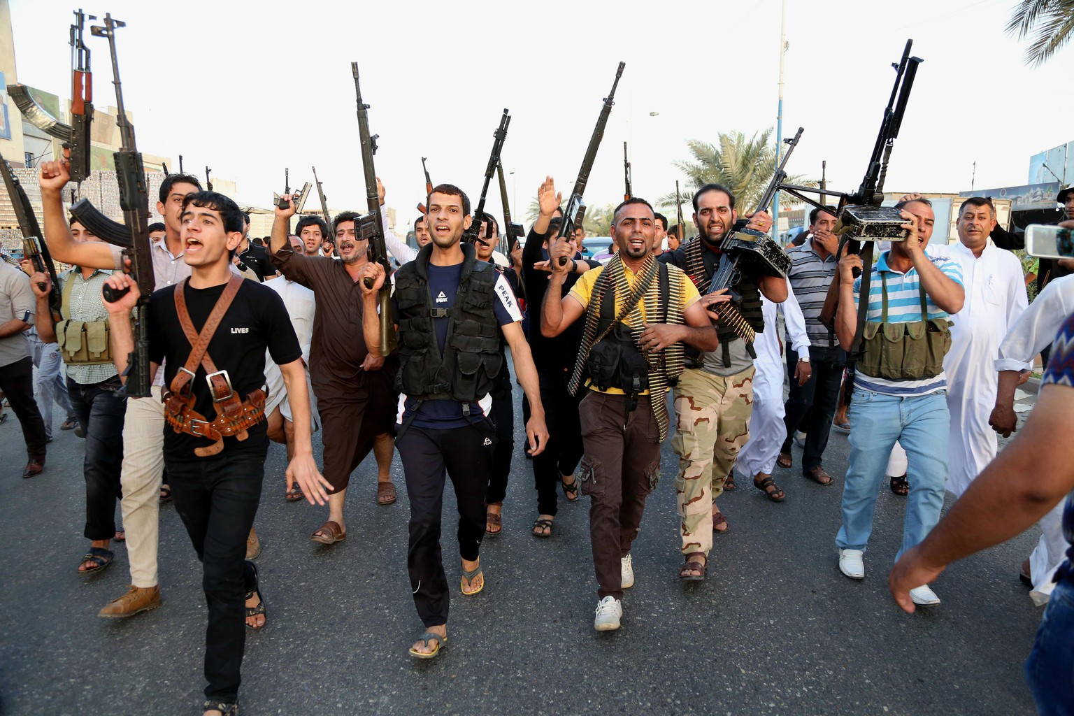 Iraqi Shiite tribal fighters deploy with their weapons while chanting slogans against the al-Qaida inspired Islamic State of Iraq and the Levant (ISIL), to help the military, which defends the capital in Baghdad's Sadr City, Iraq, Friday, June 13, 2014. The tribal leaders met in Sadr city on Friday and declared their readiness along with their tribesmen to take up arms against the al-Qaida inspired group that has made advances in Iraq's Sunni heartland .(AP Photo/ Karim Kadim)