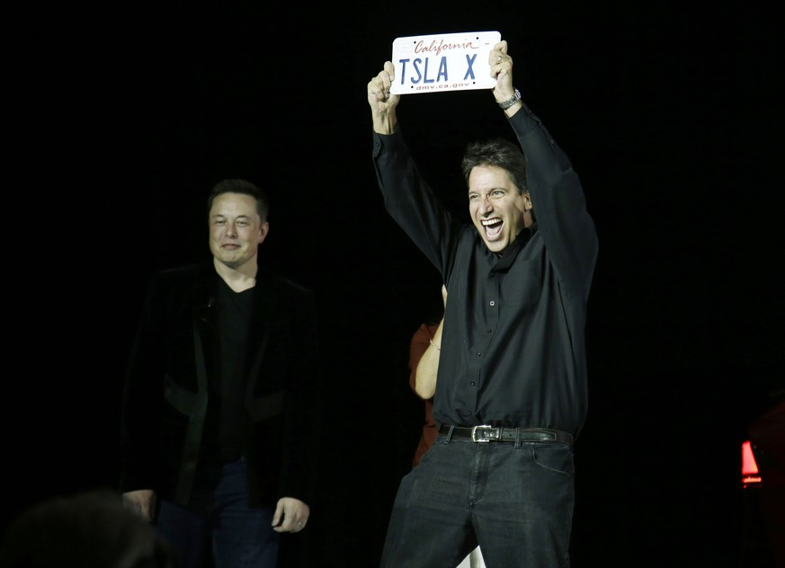 A new Tesla Model X owner celebrates after getting his keys from Elon Musk, at left, CEO of Tesla Motors Inc., during the vehicle's unveiling at the company's headquarters Tuesday, Sept. 29, 2015, in Fremont, Calif. (AP Photo/Marcio Jose Sanchez)