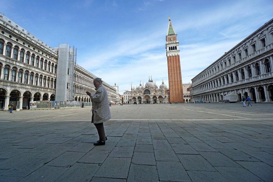 A woman walks in St. Mark's Square in Venice, Italy, Monday, March 9, 2020. Italy took a page from China's playbook Sunday, attempting to lock down 16 million people — more than a quarter of its population — for nearly a month to halt the relentless march of the new coronavirus across Europe. Italian Premier Giuseppe Conte signed a quarantine decree early Sunday for the country's prosperous north. Areas under lockdown include Milan, Italy's financial hub and the main city in Lombardy, and Venice, the main city in the neighboring Veneto region. (Anteo Marinoni/LaPresse via AP)