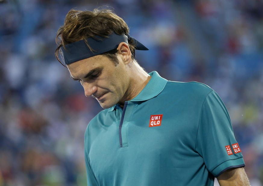 Roger Federer, oif Switzerland, packs up as rain begins to fall during the second set of his match against Juan Ignacio Londero, of Argentina, at the Western & Southern Open tennis tournament in Mason, Ohio, Tuesday, Aug. 13, 2019. (Sam Greene/The Cincinnati Enquirer via AP)