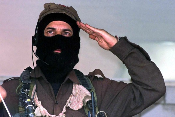 Subcommander Marcos, rebel leader of the Zapatista National Liberation Army (EZLN), sings the EZLN anthem at the closing of a rally in the Metropolitan Autonomous University of Azcapotzalco in Mexico City, Mexico, on March 20, 2001. Subcomandante Marcos, the mysterious masked leader of Mexico's Zapatista rebels, said on May 25, 2014, that he was stepping aside as chief of the 20-year-old movement. AFP PHOTO/Jorge UZON.